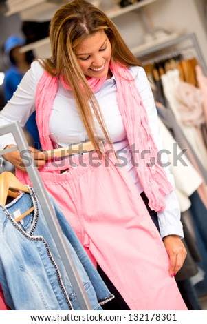 Shopping woman buying clothes and trying some pants - stock photo