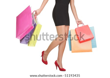 Shopping woman carrying shopping bags. lower half waist down image of sexy legs  in red high heels and colorful shopping bags. Isolated on white background. - stock photo
