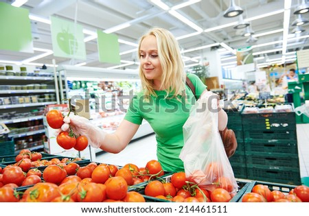 Shopping. Woman choosing bio food fruit tomato in vegetable store or supermarket - stock photo