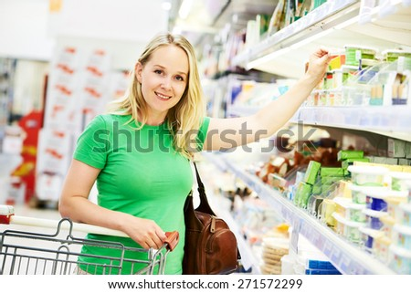 Shopping woman choosing bio food products in dairy store or supermarket shop - stock photo