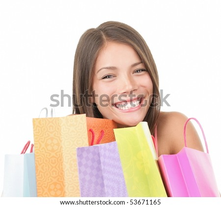 Shopping woman cute behind many shopping bags. Isolated on white background. mixed Chinese Asian / Caucasian female model in her 20s. - stock photo