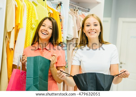 Shopping woman excited showing price tag at clothes sale in clothing store. Smiling cheerful woman. Shopping concept