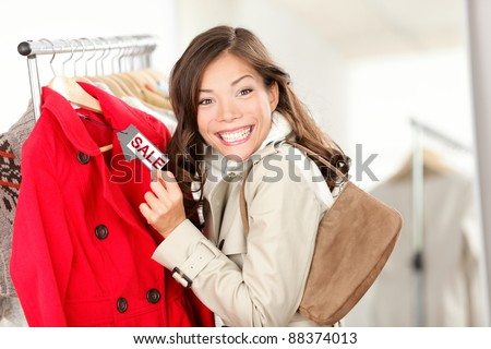 Shopping woman excited showing price tag at clothes sale in clothing store. Smiling cheerful woman. Price label reads sale.