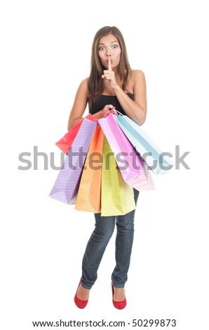 Shopping woman. Full length attractive shopping girl  holding shopping bags saying hush. Isolated on white background. - stock photo