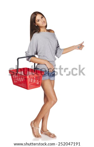 Shopping woman. Full length casual young woman standing smiling with empty shopping cart basket and gesturing thumb up sign, over white background - stock photo