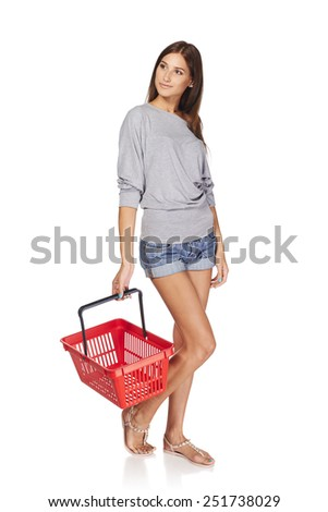 Shopping woman. Full length casual young woman standing with empty shopping cart basket and looking away at blank copy space, over white background - stock photo