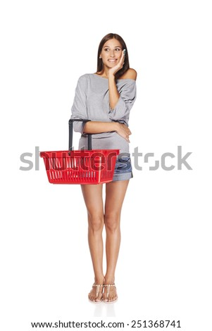 Shopping woman. Full length of surprised casual young woman standing smiling with empty shopping cart basket looking out of frame, over white background - stock photo