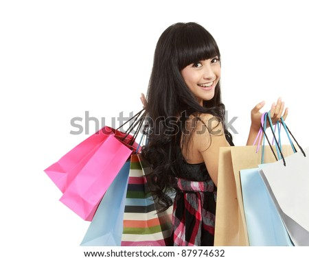 Shopping woman happy smiling holding shopping bags isolated on white background. Lovely fresh young Asian female model.