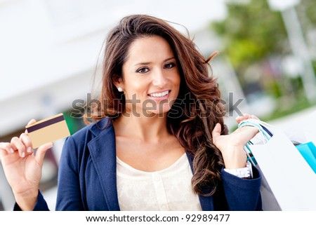 Shopping woman holding a credit or debit card - stock photo