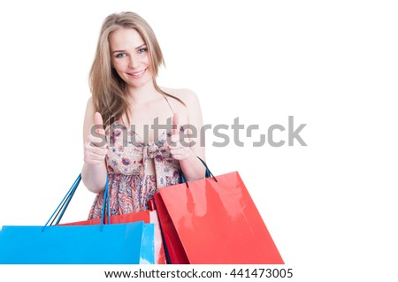Shopping woman holding colorful bags and showing double like or thumbup gesture with copyspace area isolated on white background - stock photo