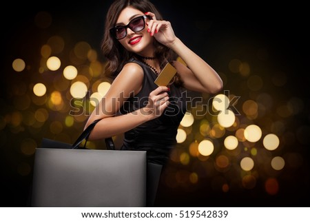 Shopping woman holding grey bag on new year background with lights bokeh in black friday holiday
