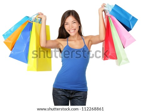 Shopping woman holding shopping bags above her head smiling happy during sale shopping spree. Beautiful young female shopper isolated on white background.