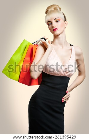 Shopping woman holding shopping bags isolated on beige background. Confident blonde girl boasting purchases. Pinup hairstyle, fringe and pink bow. Happy fashionable shopaholic. Glamorous bright makeup - stock photo