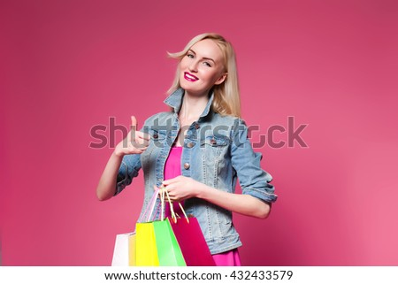 Shopping woman holding shopping bags on pink background . shows sign of cool - stock photo