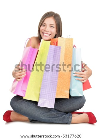 Shopping woman holding shopping bags sitting on the floor being very happy after the sale. Beautiful cute looking mixed Chinese Asian / Caucasian young woman model isolated on white background. - stock photo