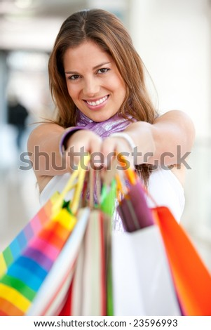 Shopping woman holding some bags in front of her face - stock photo