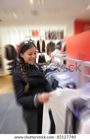 Shopping woman in clothing store buying clothes. Candid photo of Asian Caucasian woman. - stock photo