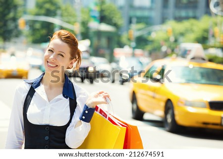 Shopping woman in New York City. Beautiful happy summer shopper holding shopping bags walking outside smiling with yellow taxi cab in background. Positive emotions. Caucasian model on Manhattan, USA. - stock photo