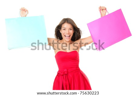 Shopping woman in red dress showing shopping bags with copy space for sign or text. Beautiful excited young mixed race female model isolated on white background. Asian Chinese and Caucasian ethnicity. - stock photo