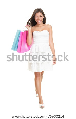 Shopping woman in summer dress holding shopping bags walking elegant in full length. Gorgeous and fresh young mixed race ethnic female model isolated on white background. Asian Caucasian ethnicity. - stock photo