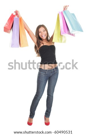 Shopping woman isolated happy holding shopping bags up in joy. Studio portrait of Asian / Caucasian shopper standing in full length isolated on white background.