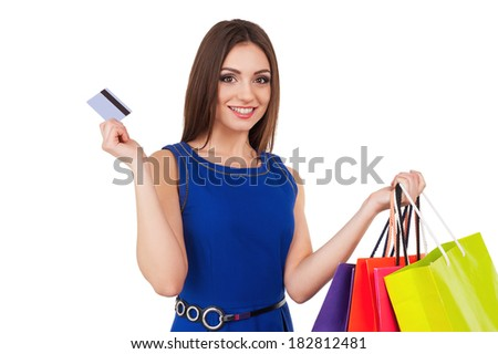 Shopping woman. Laughing young lady holding credit card and shopping bags - stock photo