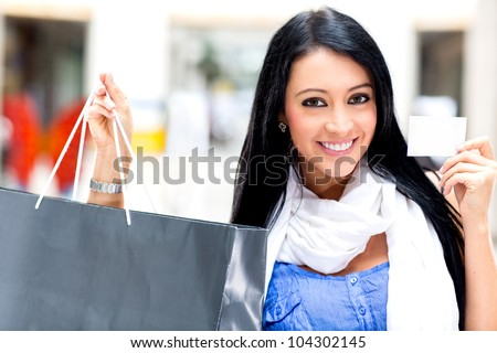 Shopping woman paying by card and holding bags - stock photo