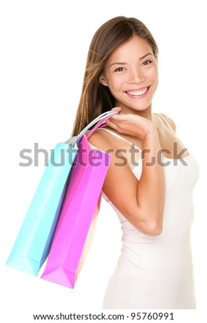 Shopping woman. Shopper girl holding shopping bags smiling happy and fresh. Beautiful cheerful mixed race Caucasian / Chinese Asian female shopping model isolated on white background.
