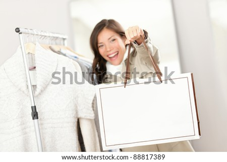 Shopping woman showing shopping bag sign with copy space. Shopper looking for clothes indoors in clothing store. Beautiful happy excited and smiling mixed race Asian Caucasian female model inside. - stock photo