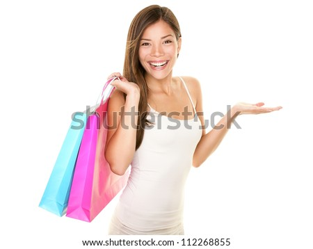 Shopping woman showing something with open hand palm smiling joyful and happy holding shopping bags. Fresh and beautiful young mixed race Caucasian / Asian female shopper isolated on white background.