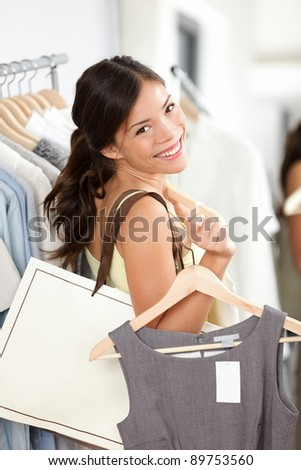 Shopping woman smiling happy holding shopping bag and clothes inside in clothing retail store. Beautiful brunette female model indoors. - stock photo