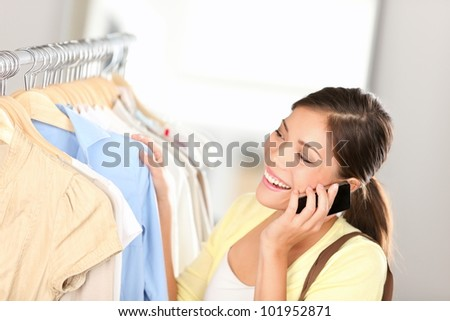 Shopping woman talking on phone joyful and happy shopping for clothes inside in clothing shop. Beautiful young multiethnic Asian Chinese / Caucasian female shopper.