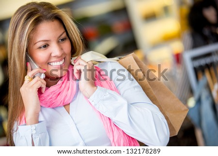 Shopping woman talking on the phone and looking happy - stock photo