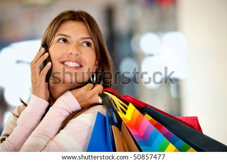 Shopping woman talking on the phone and smiling