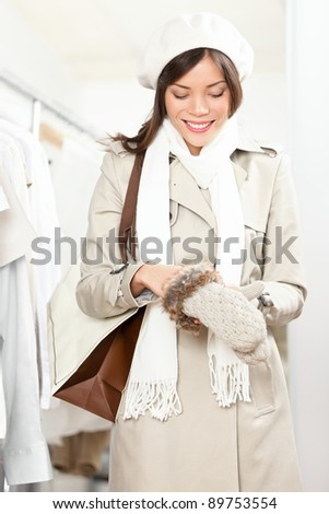 Shopping woman trying winter gloves in clothes store. Shopper woman in coat winter shopping indoors in clothing store. Beautiful mixed race Asian Cauasian female model.