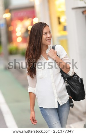 Shopping woman walking in Harajuku street, Tokyo. Young lady or female tourist window shopping in famous Takeshita street for fashion trends in Asia. - stock photo