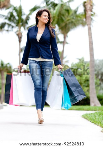 Shopping woman walking outdoors and holding bags - stock photo