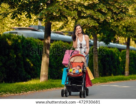 shopping Woman With Baby Carriage Using Cell Phone