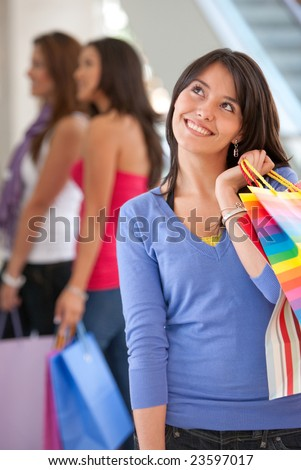 Shopping woman with bags in a mall and some friends behind her - stock photo