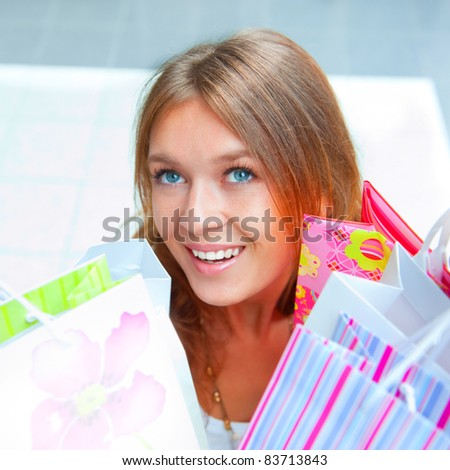 Shopping woman with lots of bags smiles inside mall. She is happy about huge christmas preseason discounts