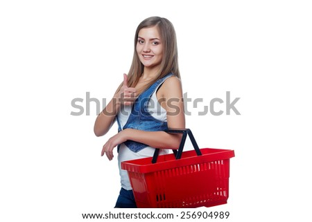 Shopping woman. Young woman standing smiling with empty shopping cart basket and gesturing thumb up sign, over white background - stock photo