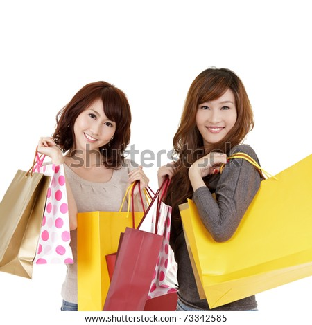 Shopping women, closeup portrait of two lady holding bags and smiling on white background. - stock photo