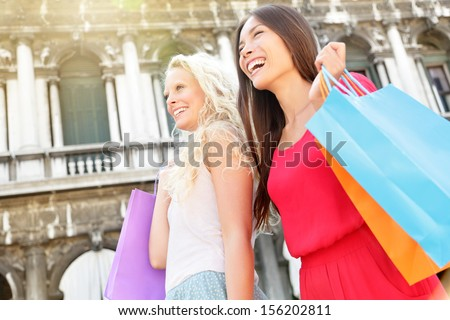 Shopping women happy holding shopping bags walking having fun laughing in street. Beautiful young Asian woman and Caucasian woman girlfriends on travel vacation, Piazza San Marco Square, Venice, Italy - stock photo