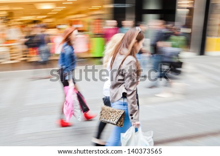 shopping women in motion blur in a shopping street of the city - stock photo
