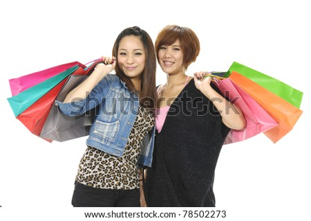 Shopping women, portrait of two lady holding bags and smiling on white - stock photo