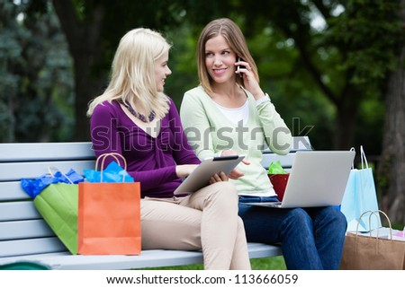 Shopping Women Using Digital Tablet, computer and cellphone on bench. - stock photo