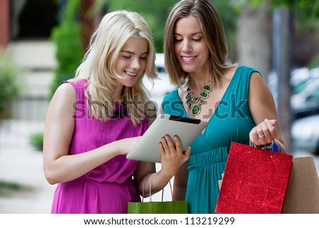 Shopping Women using Digital Tablet, outdoors.