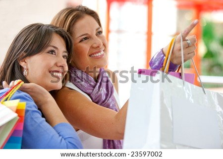 Shopping women with bags pointing out something on a shop window - stock photo