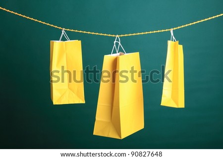 Shopping yellow gift bags on green background