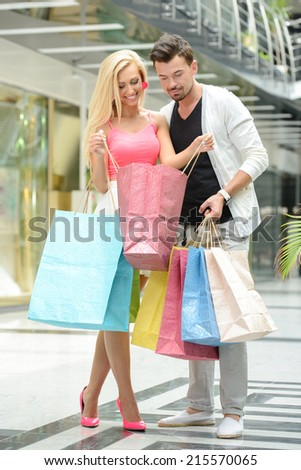 Shopping. Young beautiful couple with bags for shopping, in shopping center